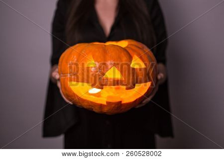 Jack O Lantern Halloween Pumpkin Grinning In The Most Evil Fashion In Woman's Hands Close Up
