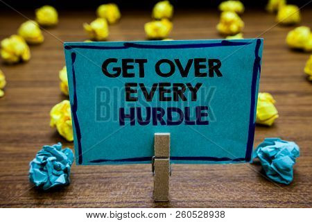 Handwriting text Get Over Every Hurdle. Concept meaning Overcome any obstacle problem trouble adversities Blurry wooden deck yellow and blue lob on ground paper clip grip page with text. poster