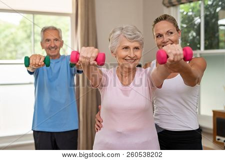 Happy senior couple exercising with dumbbells. Mature personal trainer helping elderly woman exercise at home. Old man and woman doing stretching exercise with physiotherapist.