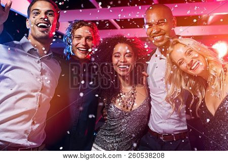 Happy young friends dancing together at party night with confetti. Group of beautiful women and elegant men and looking at camera while partying in nightclub. Group of smiling multiethnic people.