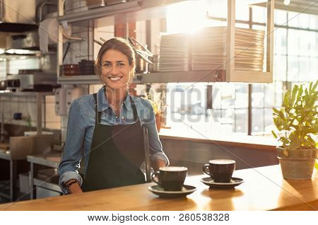 Smiling waitress wearing black apron standing behind counter in cafeteria and looking at camera. Mature woman serving two cups of coffee in cafeteria. Small business and entrepreneur concept.