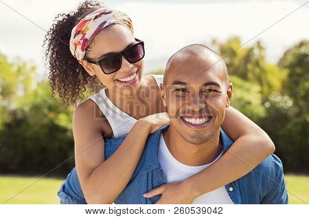 Boyfriend giving piggyback to smiling girlfriend at park and looking at camera. African american couple having fun outdoor. Smiling black woman riding piggyback on man shoulders with sunglasses.