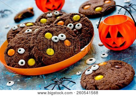 Halloween Cookies, Homemade Chocolate Cookies With Candy Eyes And Chocolate Orange And Yellow Candy,