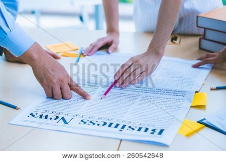 Close up hand of modern business adviser meeting to analyze and discuss the situation on the newspaper in the meeting room. Concept of Business strategy, Marketing, Analyze, Brainstorming for Business growth and successful. poster