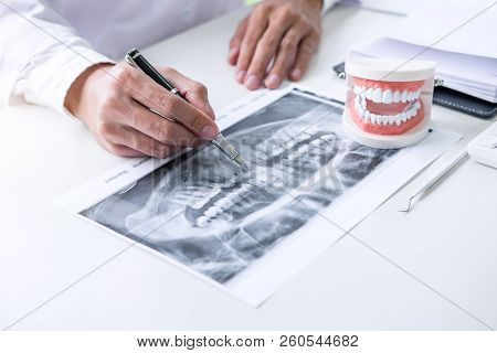 Male Doctor Or Dentist Writing Report Working With Tooth X-ray Film, Model And Equipment Used In The