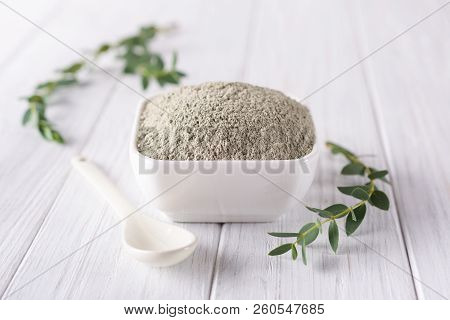 Ceramic Bowl With Green Clay Powder And Fresh Eucalyptus Leaves On White Background. Concept Of Face