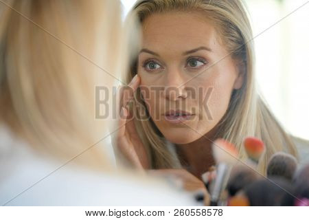 Middle-aged woman looking at her skin in front of mirror