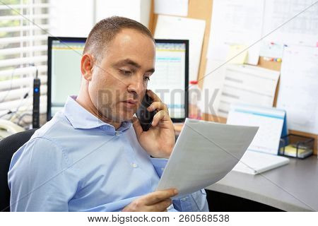 Office Worker Talking On Mobile Phone And Looking At Document While Sitting At His Working Place. Se
