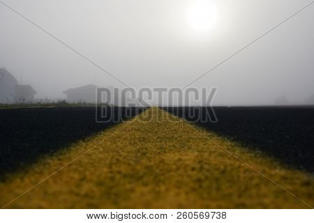 Marking On Empty Airport Runway With Buildings In A Fog. Empty Runway At Airport During A Foggy Morn