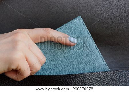 The Girl Hand Takes Out A Gray Purse From A Black Leather Bag