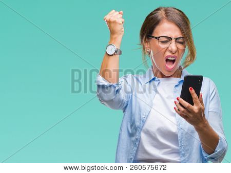 Middle age senior woman texting sending message using smartphone over isolated background annoyed and frustrated shouting with anger, crazy and yelling with raised hand, anger concept