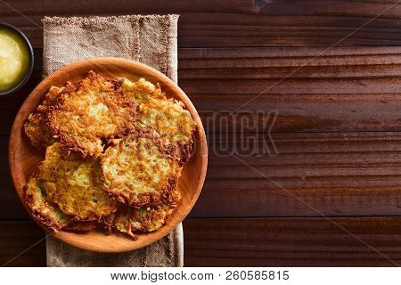 Fresh Homemade Potato Fritters Or Pancakes On Wooden Plate With Apple Sauce On The Side, A Tradition