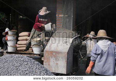 workmen mixing concrete thailand