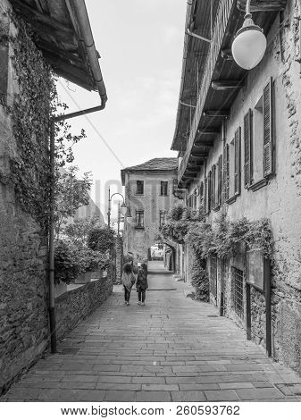 Two women stroll in the medieval village of Bard, vertical image poster