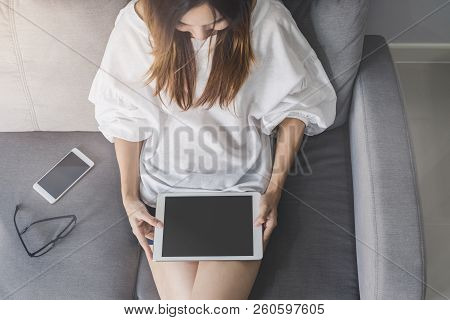 Young Asian Woman Sitting On Sofa And Using Tablet At Home