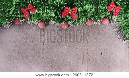 Christmas Card. Red Balls, Tinsel And Bow On A Snow-covered Wooden Background With Empty Spase