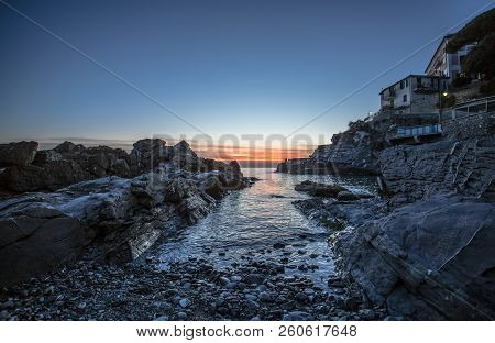 Tranquil Sea Water Surface Landscape With Rocks At Sunset, Mediterranean Sea, Italy.