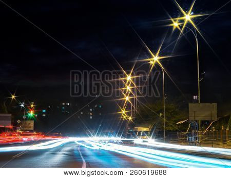 Traces Of Car Lights On The Evening Street. Starburst Of City Lights. Wide Road Leads To Living Area
