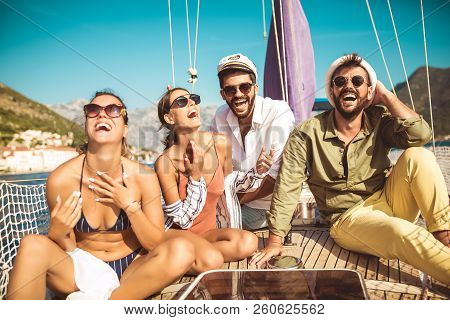 Smiling Friends Sitting On Sailboat Deck And Having Fun.vacation, Travel, Sea, Friendship And People