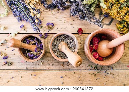 Preparation of medicinal herbs, dry flowers, ayurveda, wooden background, lavender