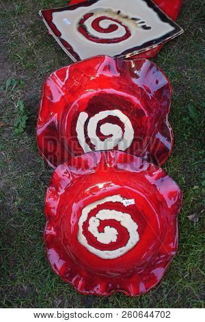 Two Red Ceramic Plates With A White Spiral Drawn Resting On The Grass And Very Typical Of Galicia, S