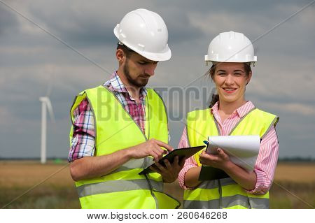 Two Successful Ambitious Young Architects In A Green Vest And White Hard Hat Designing A Plan Agains
