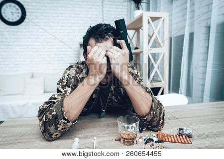 A Man In Camouflage At Home With Shotgun. Depression After War Concept. Sad Homecoming. Returning Fr