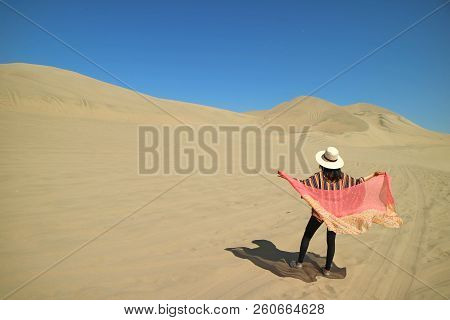 Female Putting On Her Scarf On The Windy Day At Huacachina Desert In Ica Region Of Peru, South Ameri