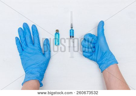 Doctor Hands In Medicinal Gloves Showing A Thumbs Up Sign And A Syringe With Blue Liquid Medicine On