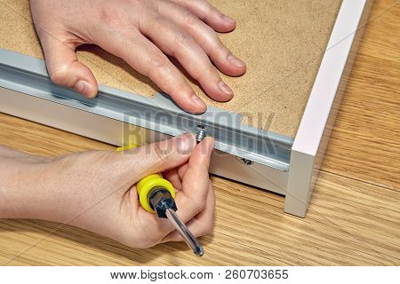 Use Of Furniture Fasteners When Assembling A Drawer, Hands Of A Furniture Builder Close-up.