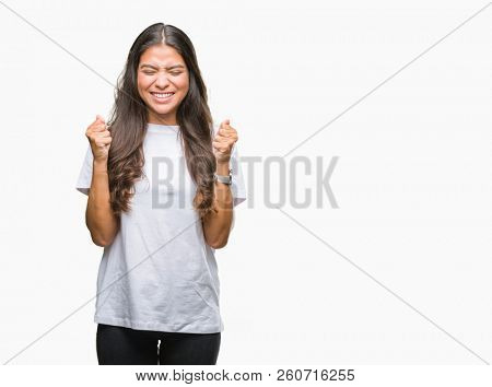 Young beautiful arab woman over isolated background excited for success with arms raised celebrating victory smiling. Winner concept.