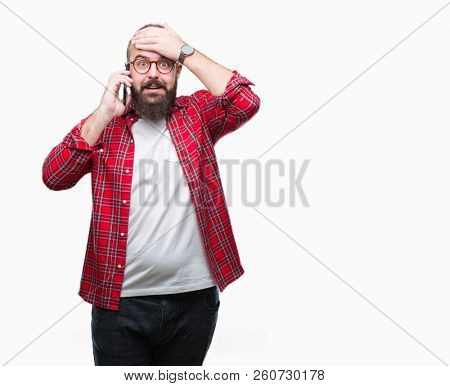 Young caucasian hipster man talking on smartphone over isolated background stressed with hand on head, shocked with shame and surprise face, angry and frustrated. Fear and upset for mistake.