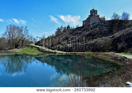 Europe, Croatia/  Cliffs, Church And Beautiful Lake Surrounded Whit Mountain/ Orthodox Church At The