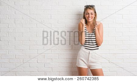 Young beautiful blonde woman over white brick wall excited for success with arms raised celebrating victory smiling. Winner concept.