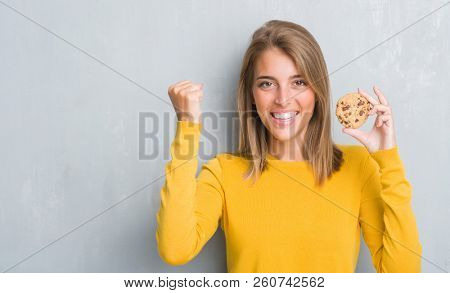 Beautiful young woman over grunge grey wall eating chocolate chip cooky screaming proud and celebrating victory and success very excited, cheering emotion