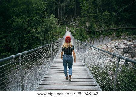 Young Hiker Woman Walks On Suspension Bridge