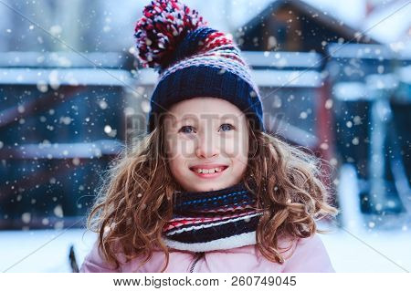 Winter Portrait Of Happy Child Girl Playing Outdoor In Snowy Garden. Seasonal Holidays And Vacations
