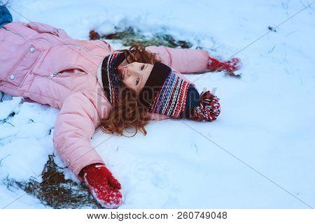 Winter Portrait Of Happy Child Girl Playing Outdoor In Snowy Garden, Making Snow Angel. Seasonal Hol