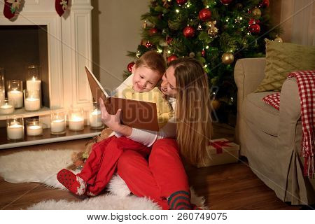 Family Of A Boy And His Mom Are Reading A Nice Book Laughing Together, Cozily Decorated Christmas Ro