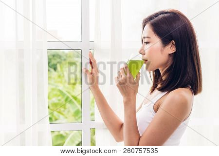 Woman Enjoy Healthy Drinking Green Detox Vegetable Juice Near Window Curtains In The Living Room At