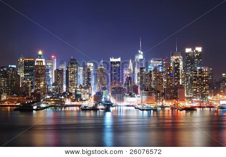 Mordern city night scene. New York City Times Square Manhattan Skyline at night panorama over Hudson River with reflection.