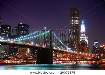 Puente de Brooklyn de Nueva York y Manhattan skyline con rascacielos sobre río Hudson iluminado w
