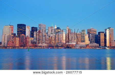 Manhattan Skyline at dusk, New York City, with lights in offices buildings over Hudson River.