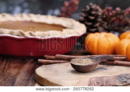 Pumpkin Pie Spice Measured In A Wooden Spoon Over A Rustic Wooden Background. Pie And Pumpkins In Th