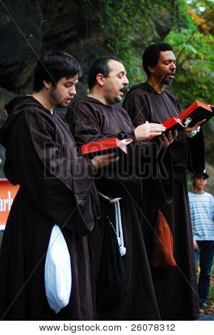 NEW YORK CITY - OCT 3: Men read bible in group in New York Medieval Festival. October 3, 2010 in Ft. Tryon park; Manhattan, New York City.