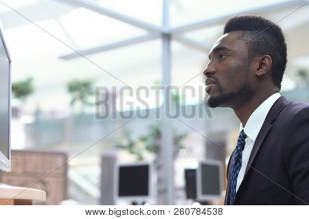 Portrait Of Successful African-american Businessman Sitting At Desk With Computer In Office.