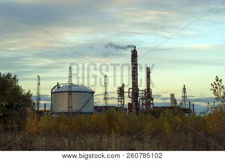 Industrial landscape - working fractionating columns and a tank for storing oil products under the evening sky poster