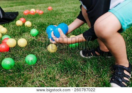 Colored Plastic Toy Balls Spilled In The Grass. Boy Gethering Blue Balls. Baby Birthday Party Activi