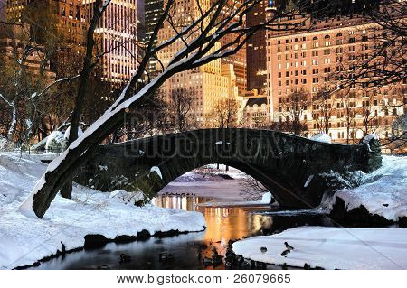 New York City Manhattan Central Park panorama in winter with snow, bridge; freezing lake and skyscrapers at dusk.