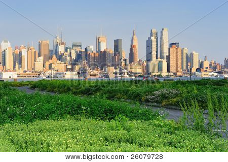 New York City Manhattan midtown skyline view from New Jersey Hudson River waterfront park with green lawn at sunset.